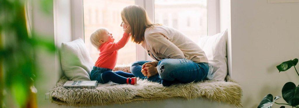 Kvinna och barn sitter på fönsterkarm vid element